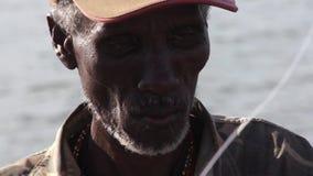 Man of the tribe elmolo prepares fishing rod stock video