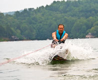 Man on Trick Ski Pulling Up. A man on a trick ski being pulled up out of the water Stock Image