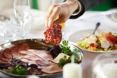 Man tries meat appetizer from a silver plate.  Stock Photography