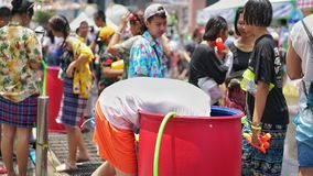A man tries to get water in the tank in Songkran festival stock photography