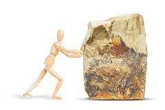Man tries to move a huge rock. Abstract image with a wooden puppet Royalty Free Stock Photography
