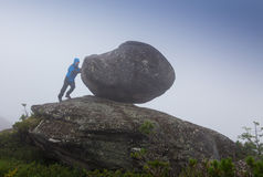 Man tries to move the stone hanging. In the mountains in a  fog Stock Images