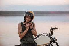 Man tries to put off his helmet sitting on motorcycle Stock Photos