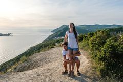 Man tries to raise a woman who resists on the mountain with seascape. Front view. Royalty Free Stock Images