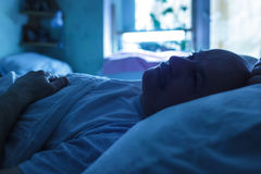 Man tries to sleep at night. An elderly man suffers from insomnia, trying to sleep. Backlight image in blue tones Royalty Free Stock Photography