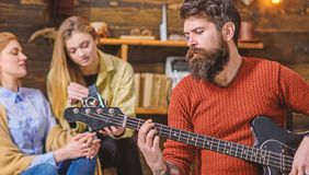 Man with trimmed beard and mustache holding electrical guitar. Musician in terracotta pullover wearing trendy watch and stock image