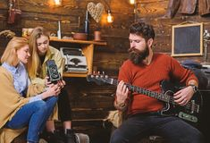 Man with trimmed beard playing electrical guitar. Rock musician spending time with family in countryside. Bearded man. Man with trimmed beard playing electrical stock photography