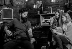 Man with trimmed beard playing electrical guitar. Rock musician spending time with family in countryside. Bearded man. Man with trimmed beard playing electrical royalty free stock image
