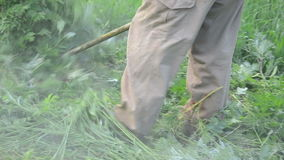 Man trimmer cut grass. Turn view man worker with trimmer mow cuts weeds in garden after rain. Water drops rise up stock footage