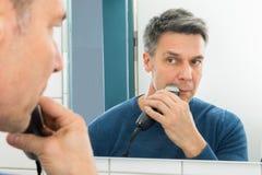 Man trimming beard Stock Image