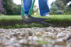Man trimming edge of grass with garden tool, low section Royalty Free Stock Photo