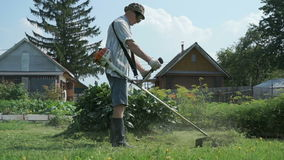 Man trimming grass in the garden using lawnmower stock footage