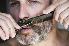 Man trimming his beard. Closeup of handsome man trimming his beard Stock Photo