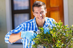 Man trimming shrub. Cheerful young man trimming a shrub in front of house Royalty Free Stock Photos