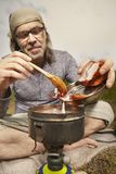 Man on trip relaxing and cooking in nature stock image