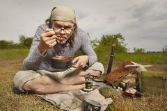 Man on trip relaxing and cooking in nature royalty free stock image