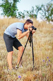 A man with a tripod and camera standing on a meadow Royalty Free Stock Photo