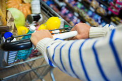 Man with trolley in grocery section. Of supermarket Royalty Free Stock Photo