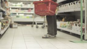 A man with a trolley in the store. A man with a basket in the store. Shelves with goods in the supermarket stock video
