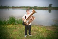 Man with trombone pipe. Make noise outdoor on lake and grass backround Stock Images