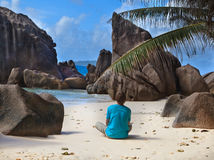 Man on tropical beach. Man sitting on tropical beach in la Digue island, Seychelles Stock Image