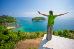 Man on tropical island cliff with small beach below Stock Photography