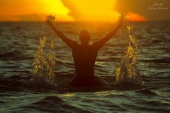A man in the tropical sea raises the spray with a wave of his ha stock images