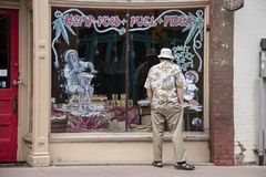 Man in tropical shirt and hat and sandals looks in painted and decorated window of closed b stock images
