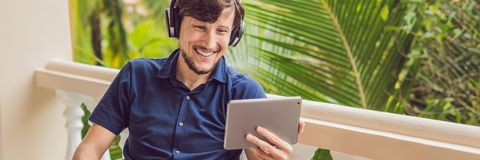 Man in tropics talking with friends and family on video call using a tablet and wireless headphones BANNER, long format. Man in the tropics talking with friends royalty free stock photo