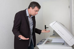 Man in trouble with the copy machine. Business man in trouble with the copy machine Royalty Free Stock Image