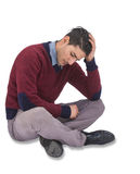 Man in trouble. A depressed looking man is sitting on the floor leaning with his head on his hand Royalty Free Stock Photos