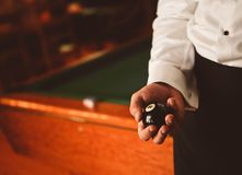 Man in trousers and a shirt is holding a billiard ball royalty free stock photo