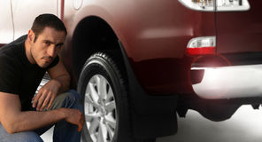 Man and truck. Portrait of a man kneeling down by large pickup truck Royalty Free Stock Image
