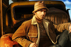 Man and Truck. Horizontal portrait of a good looking young male model in brown against a rusty old truck Stock Photo