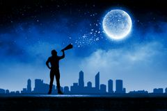 Man with trumpet. Silhouette of man screaming in trumpet at night Stock Photo