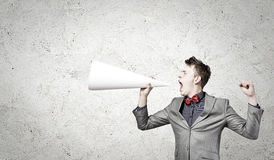 Man with trumpet. Young businessman screaming emotionally in paper trumpet Royalty Free Stock Photography