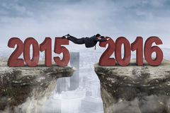 Man try to through the gap with numbers 2015 and 2016 Stock Images