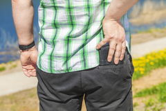 Man try to put purse in trouser pocket Royalty Free Stock Photo