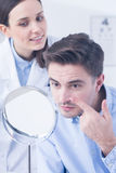 Man trying on contact lens. Professional optician and men trying on contact lens Royalty Free Stock Images