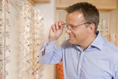 Man trying on eyeglasses at optometrists. Smiling Stock Photos