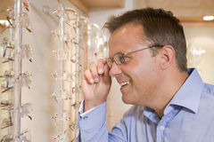 Man trying on eyeglasses at optometrists. Smiling Royalty Free Stock Image