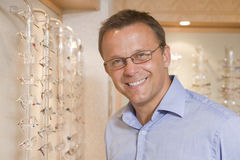 Man trying on eyeglasses at optometrists. Smiling Royalty Free Stock Images