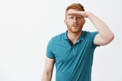 Man trying find joke, looking far away, squinting and holding palm on forehead to cover eyes from sunlight and see stock images