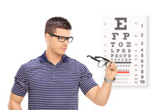 Man trying on glasses in front of an eye chart Stock Photos