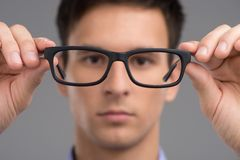 Man trying glasses to improve vision. Royalty Free Stock Photography