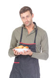Man trying his hand at baking. Attractive man trying his hand at baking wearing an apron and carrying a bowl of freshly baked cookies isolated on white Royalty Free Stock Images
