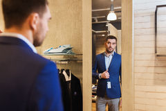 Man trying jacket on at mirror in clothing store. Sale, shopping, fashion, style and people concept - elegant young man choosing and trying jacket on and looking Royalty Free Stock Image