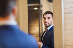 Man trying jacket on at mirror in clothing store Royalty Free Stock Photos
