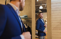 Man trying jacket on at mirror in clothing store Stock Images