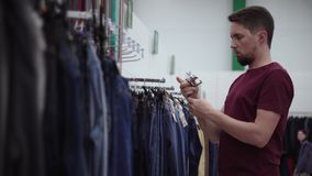 Man is trying leather belt in clothing store